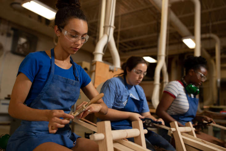 Savannah Smith, Jamie Schlabach, and Sophia Gueye use traditional shave horses to carve spindles for the Berea Basket and legs for the Forest Stool.