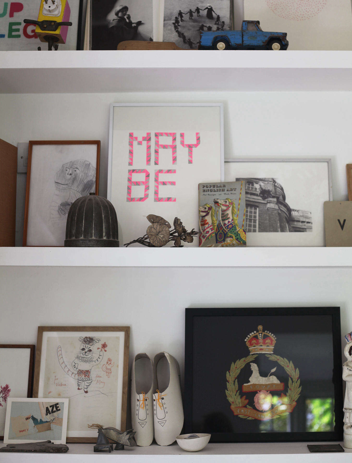 Victoria uses the sitting room bookshelves as an opportunity for display. Chinese joss paper shoes rest next to a th-century British army regiment embroidery. May Be is by illustrator Fiona Woodcock.