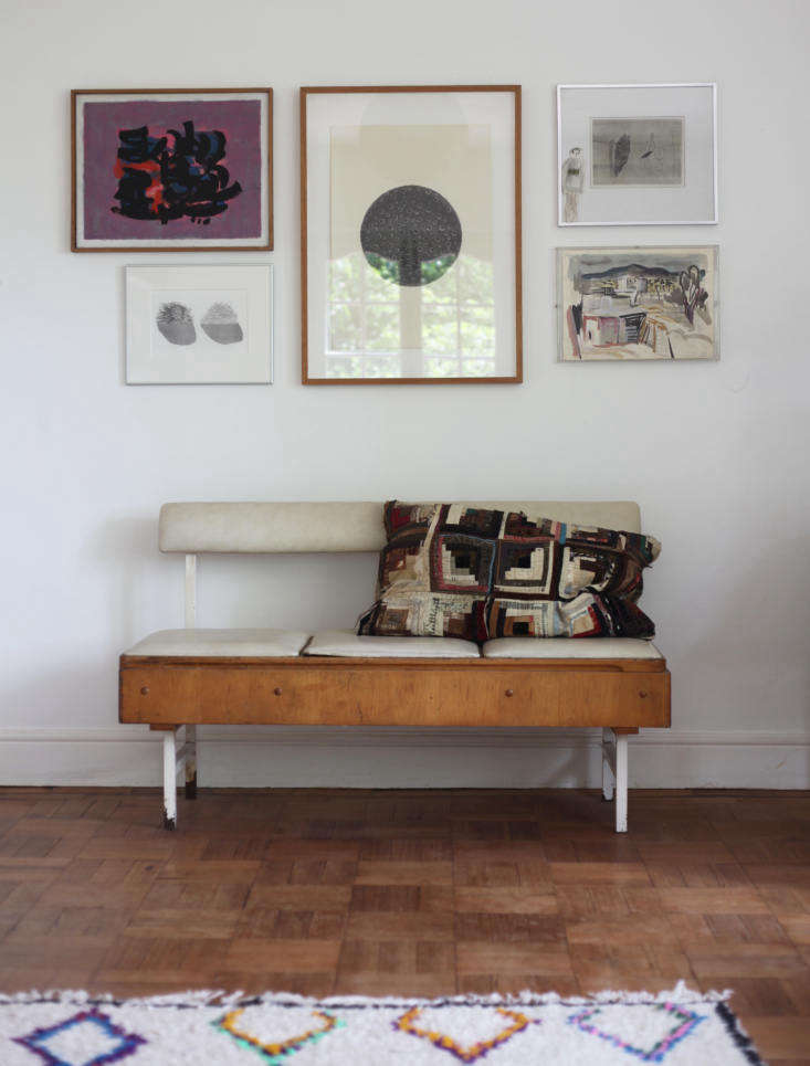 A pillow made from an antique silk log-cabin quilt rests on a vintage bench that came out of a doctor&#8