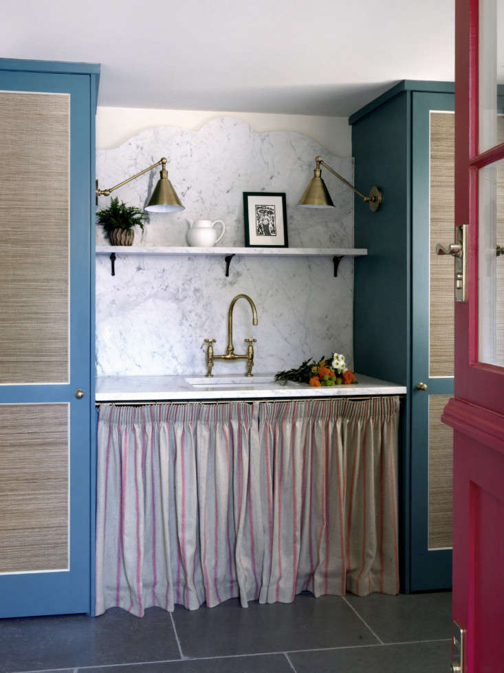 In a Sussex cottage, Beata Heuman skirted the utility sink with striped linen and detailed the marble backsplash with a subtle flourish. The seagrass-covered cabinets hold a washer/dryer and cleaning supplies.