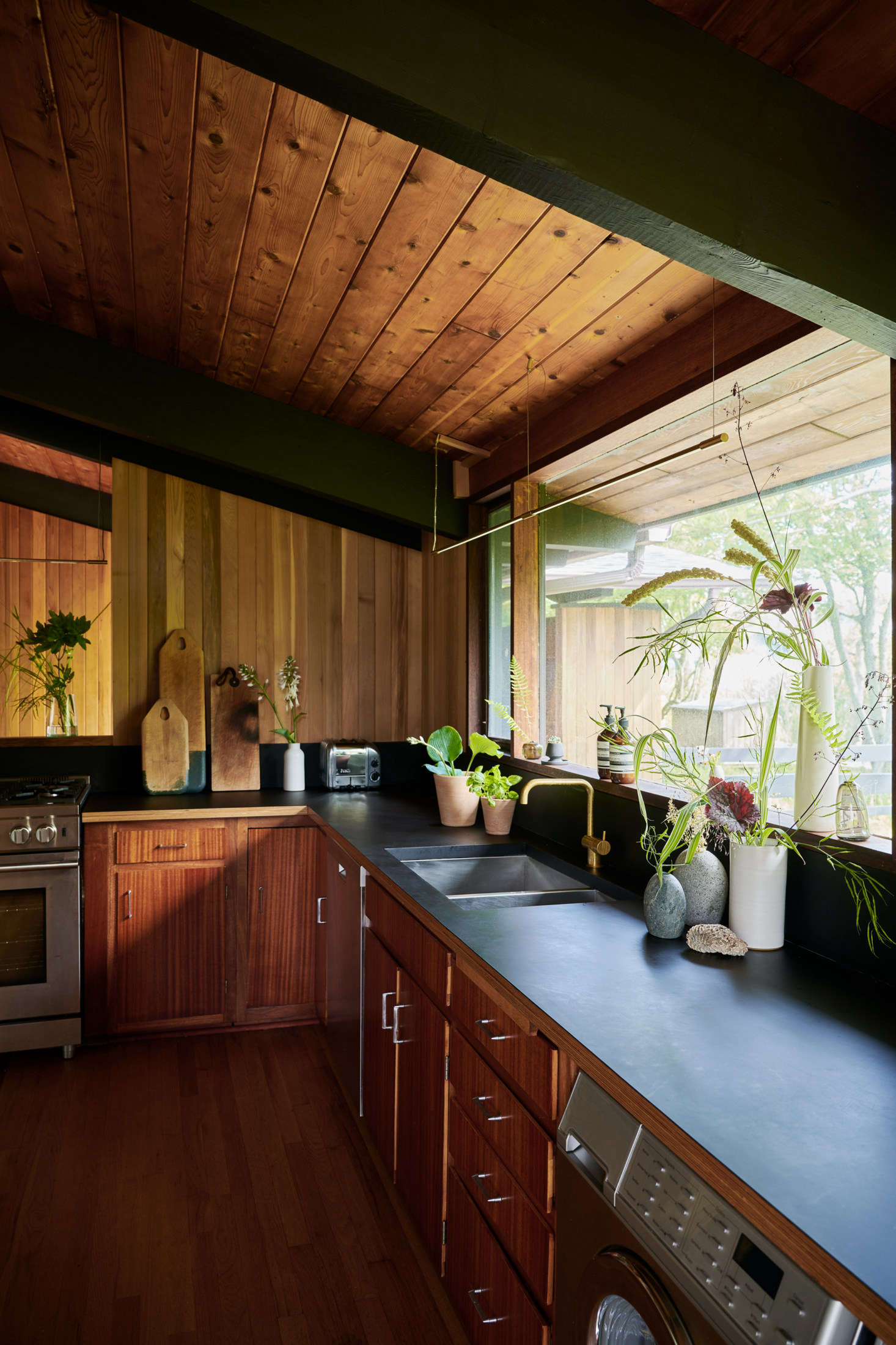 The kitchen can become a mini greenhouse, filled with botanicals of all kinds. On the counter are stems from Bloomist's dried and EcoFaux collections, including airy Dried Pepper Grass ($) and dark EcoFaux Chocolate Cosmos ($ per stem).