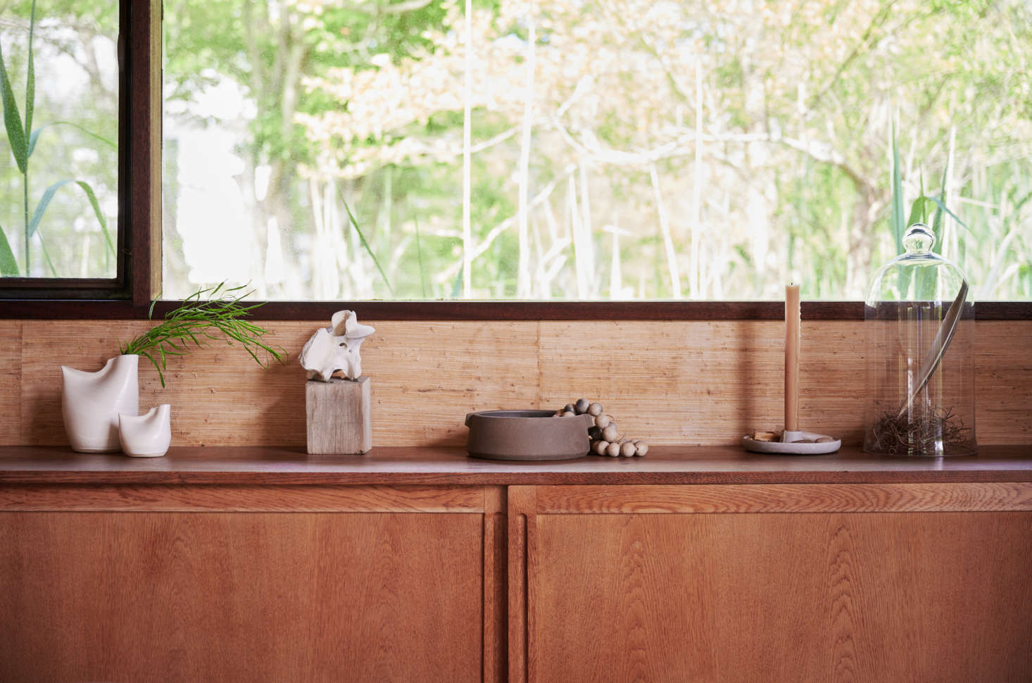 A simple vignette on a sideboard: a string of Tunisian Clay Beads ($98); a Stoneware Candlestick Holder ($68), made in Illinois; and a single beeswax candle. (We like the Beeswax Column Candles, $33 a pair, hand-poured in the Catskills.)