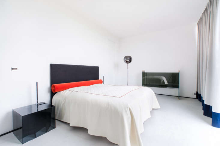The main bedroom was inspired by Polish modernism. The glass nightstand and sofa are by Glas Italia.
