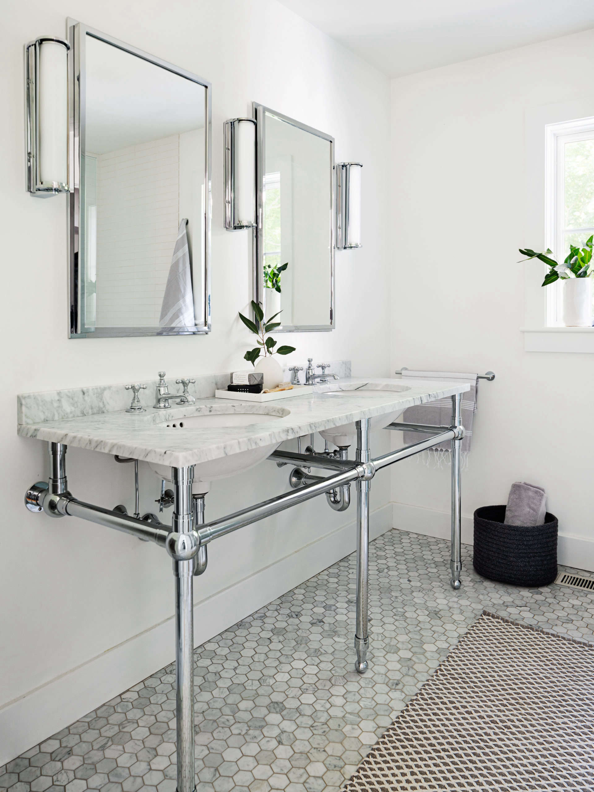 The mine-and-yours washstand is the Gramercy from Restoration Hardware with Waterworks faucets. The hexagonal marble floor tiles are from Nemo Tile.