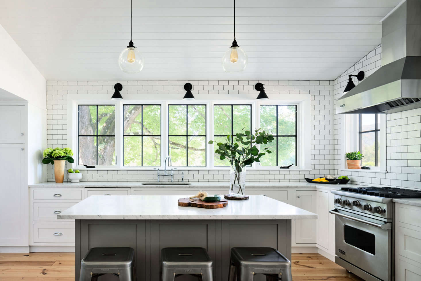 Porter set off the kitchen with subway-tiled walls and a Carrara marble-topped breakfast counter. In lieu of upper cabinets, five windows frame views of an old maple tree.