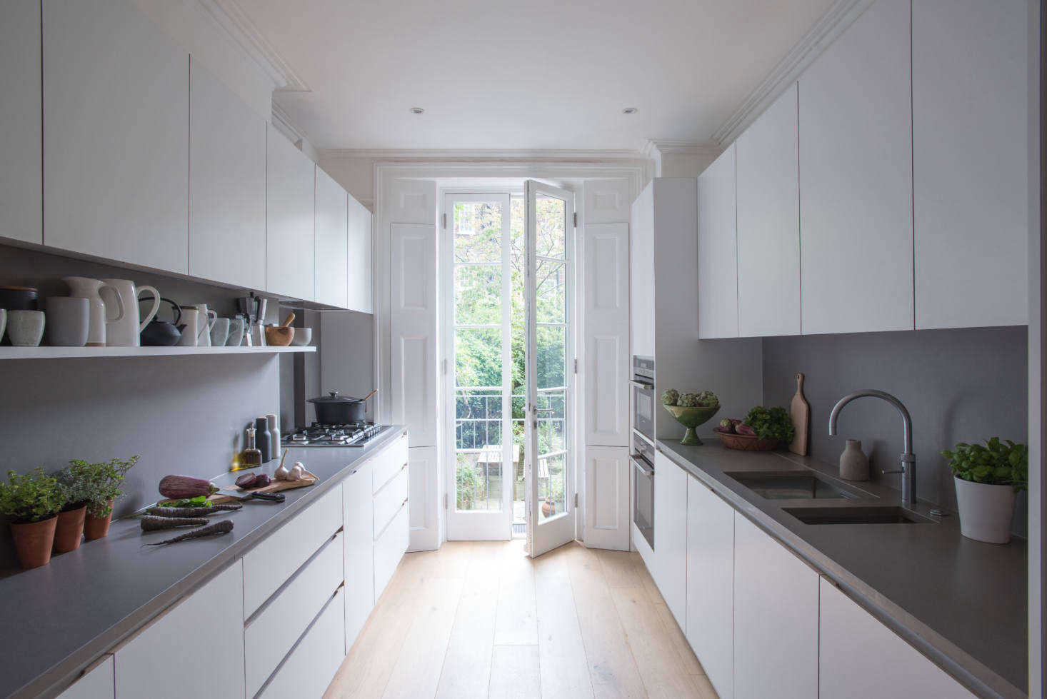 Composed of streamlined cabinets of laminate-clad MDF with oak edging, the kitchen has windows at either end: the French doors overlook an eating area and garden. The design is known as the JT Original.