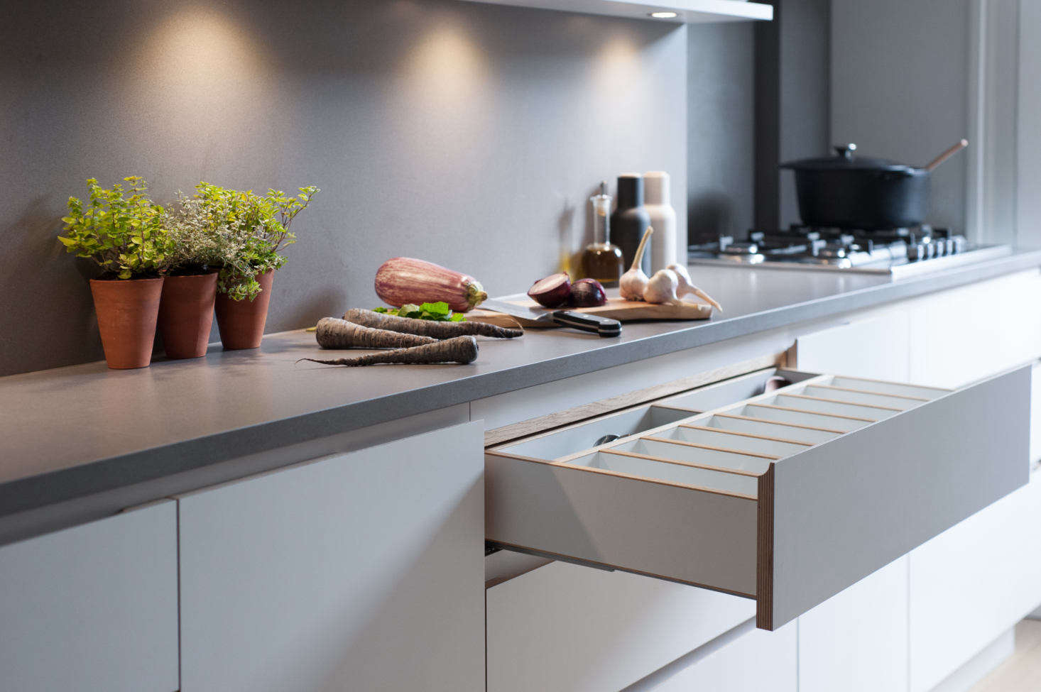 The drawers have finger scoops in lieu of hardware, and custom fittings, such as this cutlery drawer of birch plywood.