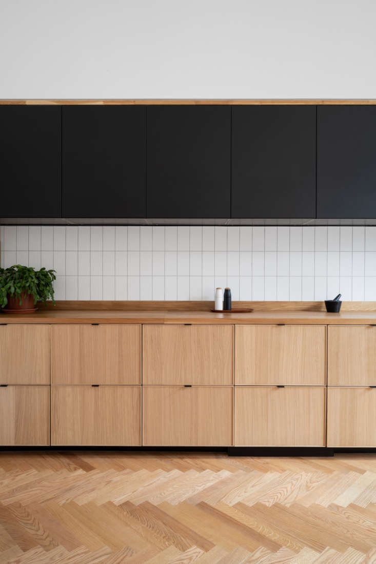 All cabinet bases and doors are from Ikea. The matte black fronts are from the Kungsbacka line, all made from recycled wood and recycled PET bottles. The lower cabinets are from the oak Ekestad series, currently unavailable in the US. Classic subway tiles (theirs are from here) look modern when installed vertically.