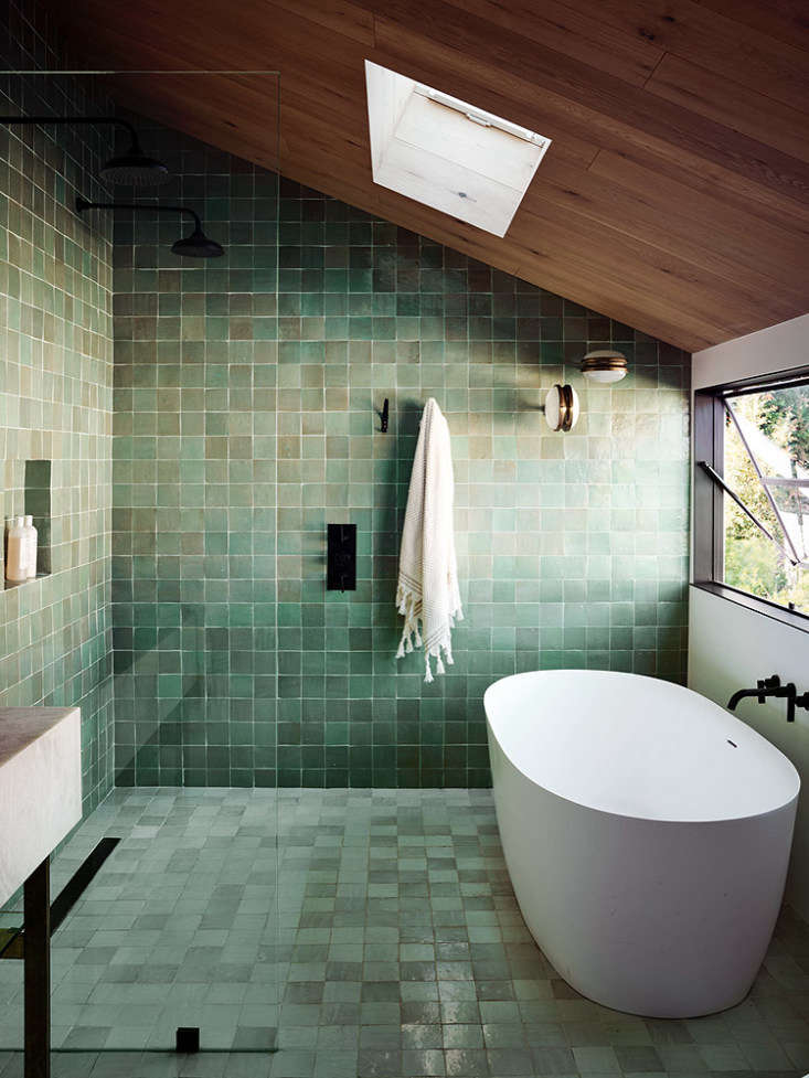 A second-floor bathroom lined with green zellige tiles.
