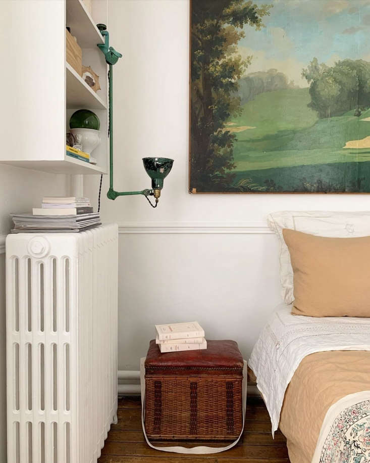 A bedroom with an unexpectedly upturned task light and basket as nightstand.