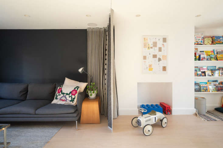 a clever curtain separates the family room from the play area. 25