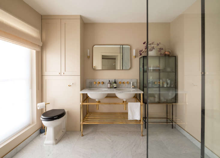 In the traditional ensuite bath, a freestanding glass and steel cabinet (the Haze Vitrine from Ferm Living) adds a contemporary touch. (For similar cabinets, see  Easy Pieces: Steel-Framed Display Cabinets.) On the walls is Farrow & Ball Joa&#8