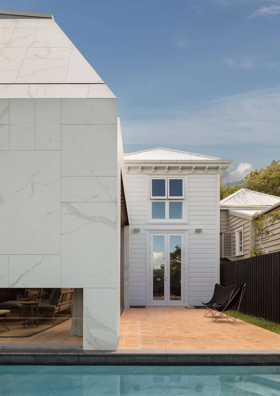 The exterior of the house shows where the original build, in white-painted wood cladding, meets the new extension, finished in broad white marble tiles. The pool is a new addition and surrounding exterior landscape, both in front and back, is by landscape designer Jared Lockhart.