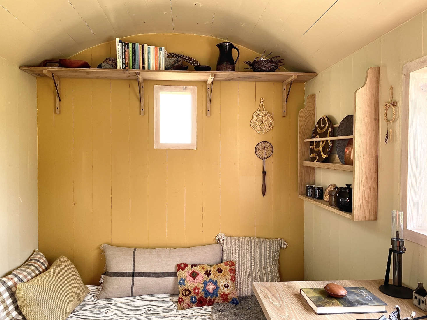 The sofa is a camp cot piled with mattresses, blankets, and pillows. The back wall introduces a bit of color to the room, which is lit by candles and Oil Lamps by Castor.