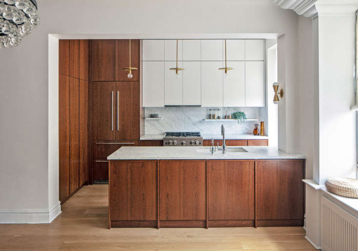 The mandate for the kitchen was plenty of storage and a sleek but inviting look: Barbara, who is from Italy, campaigned for warmth; Jakob, who is Swedish, likes logic and order. Inspired by an old mantel opposite the kitchen, the three settled on a cherry finish for the majority of the cabinets, &#8