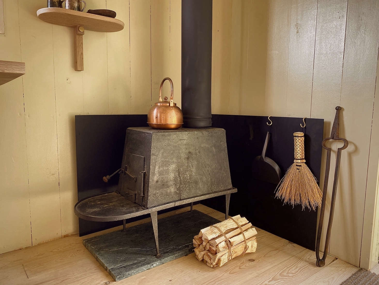 A wood-burning stove stands next to the entry. The Shaker-inspired wall shelf is a Hallgeir Homstvedt design for Mjölk known as the Doverail.