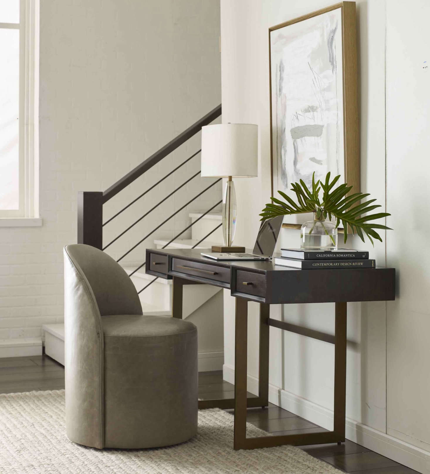The Allure Desk—shown here with a dark smoked eucalyptus top and brass base—has a slim profile but a generous surface and creates an efficient, good-looking work-from-home setup in any room.