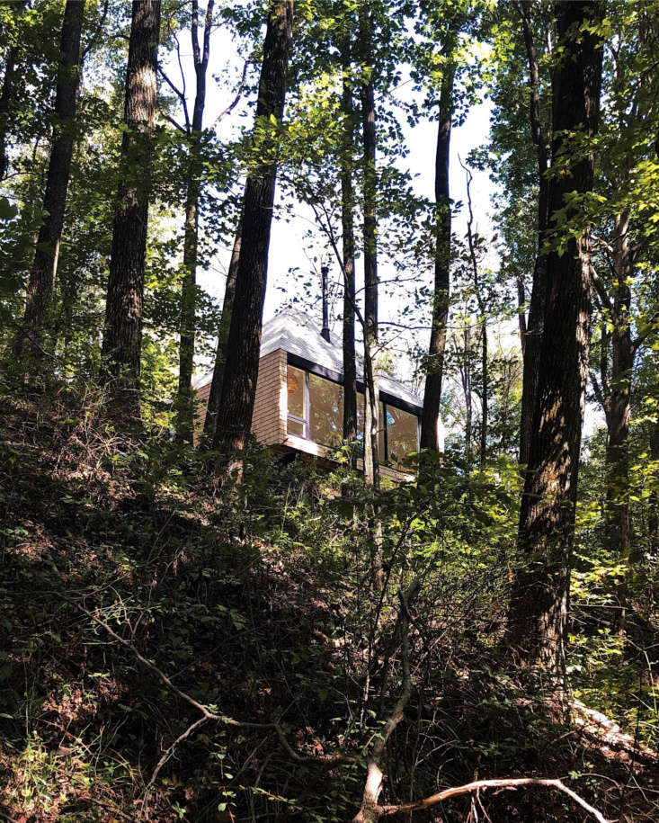 The hut-like guesthouse sits atop a wooded bank overlooking a lake. (As kids, he and his siblings used to hike here.) Untreated cedar shingles make up the exterior and will eventually turn gray over time. From the project description: &#8