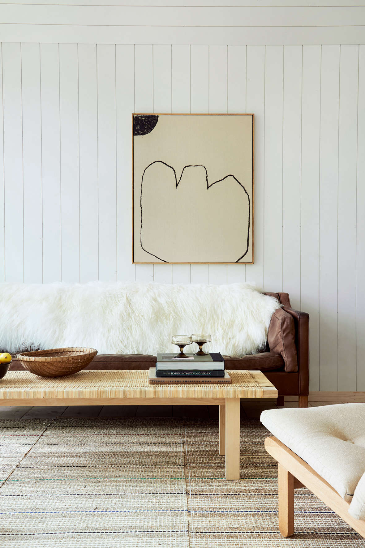 A painting by Bertrand Fournier hangs above a vintage Borge Mogensen