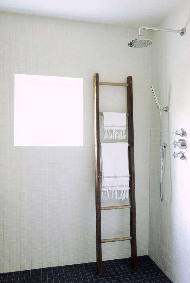 White mosaic tiles cover the rest of the walls. A vintage wooden ladder, used as a towel holder, adds some warmth to the room. The shower fixtures are by Signature Hardware.