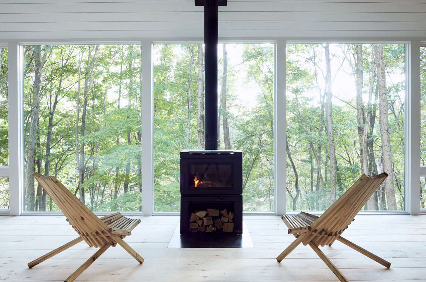 Two vintage Kentucky stick chairs (sourced on Etsy) are situated for optimal forest bathing: in front of floor-to-ceiling Andersen windows and an Osburn Matrix wood stove.