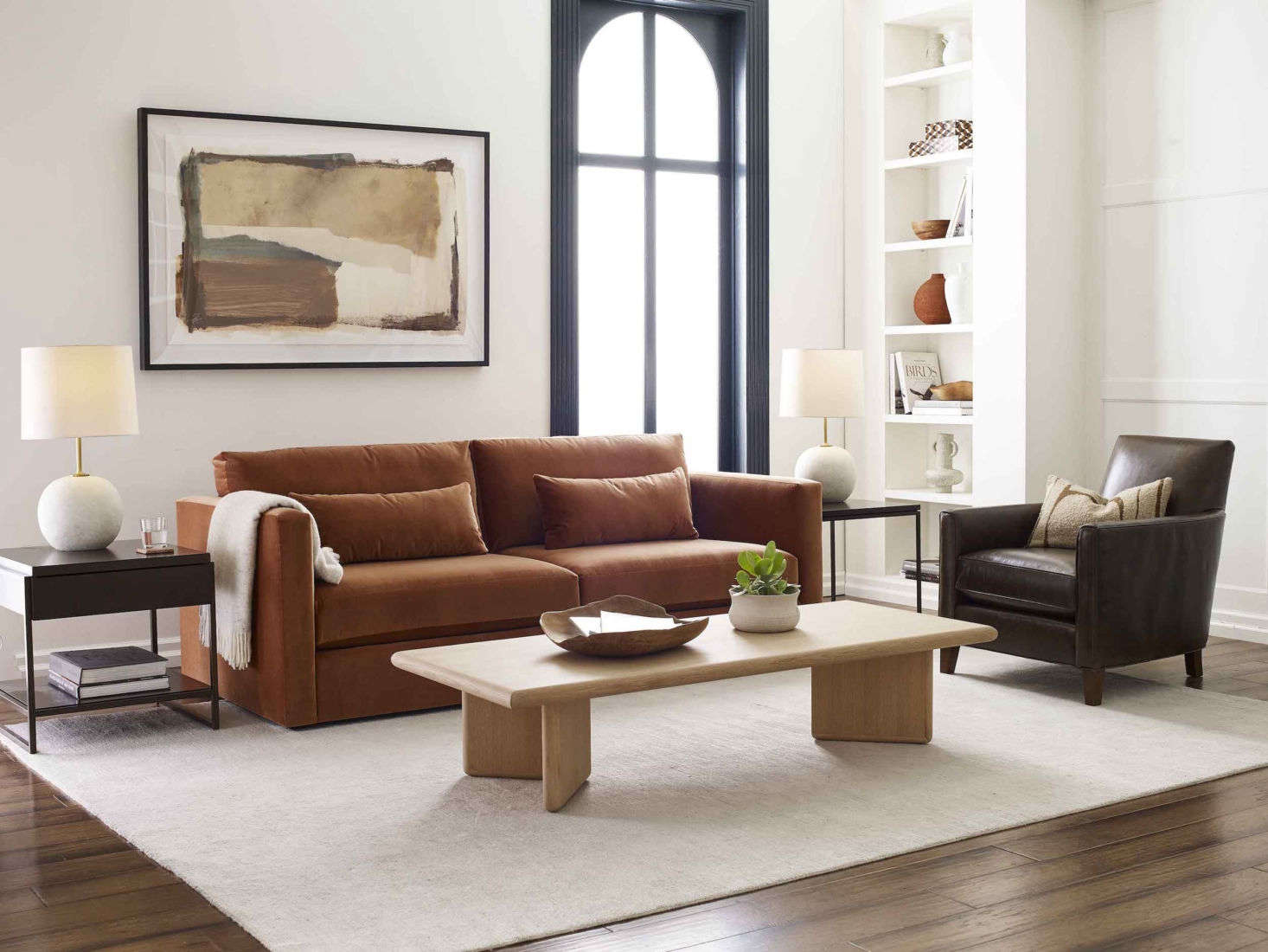 """The Haywood Sofa, shown here in rich """"boulevard auburn,"""" a performance velvet, is equal parts sturdy construction and sumptuous softness, with a low-slung design, hypoallergenic down-alternative back cushions, and """"sink-in style."""" Alongside is the Aiden Leather Chair, a standout of the MG+BW Classics Collection, a limited-edition re-release of some of the company's most iconic pieces from the past 30 years, and the Danish modern-inspired Merritt Cocktail Table."""