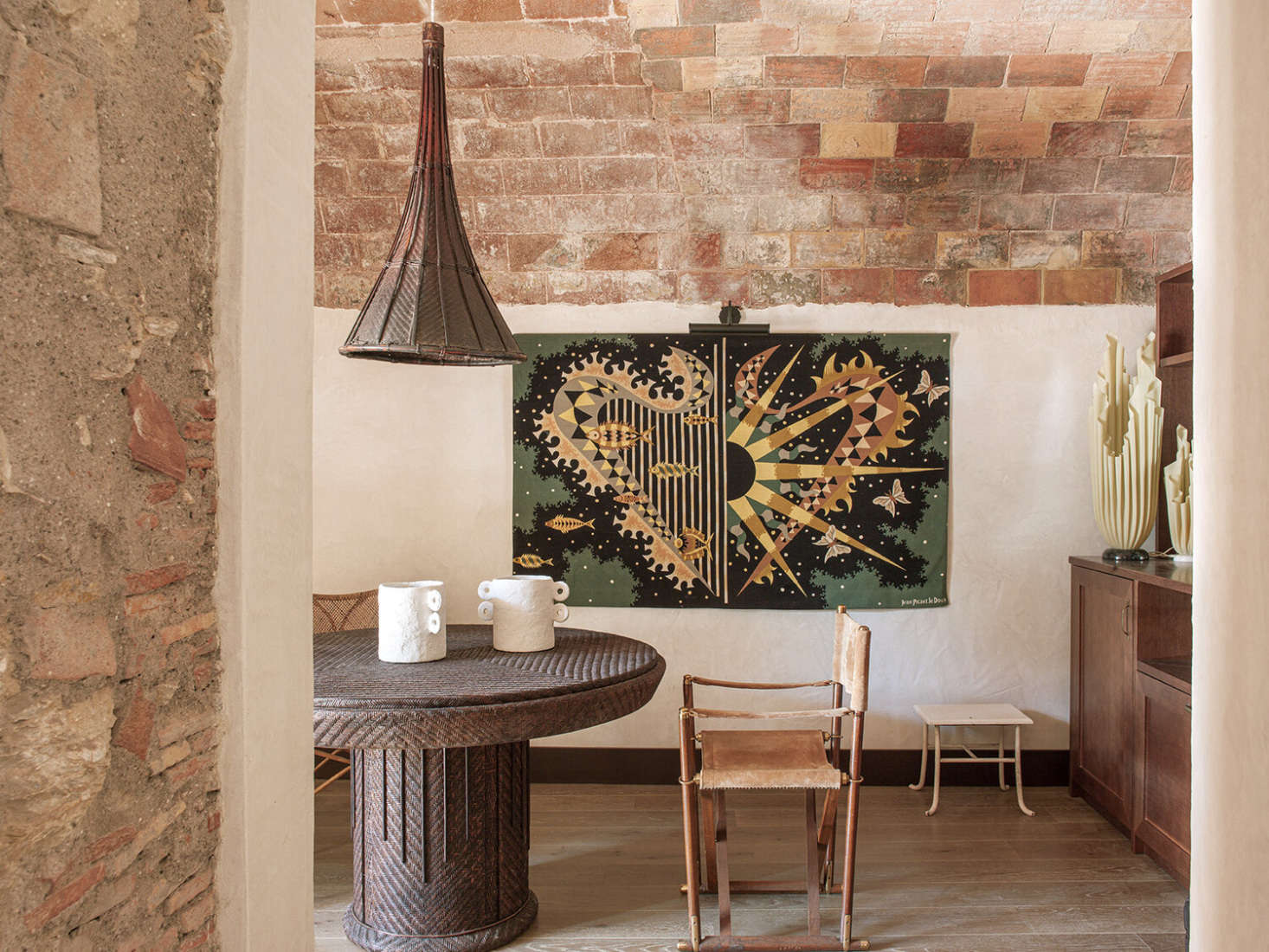 In the bar/winter breakfast area, the designers paired a rattan table found in a Barcelona antiques shop with a light made from a Vietnamese rice picker. The vintage tapestry is by Jean Picart Le Doux.