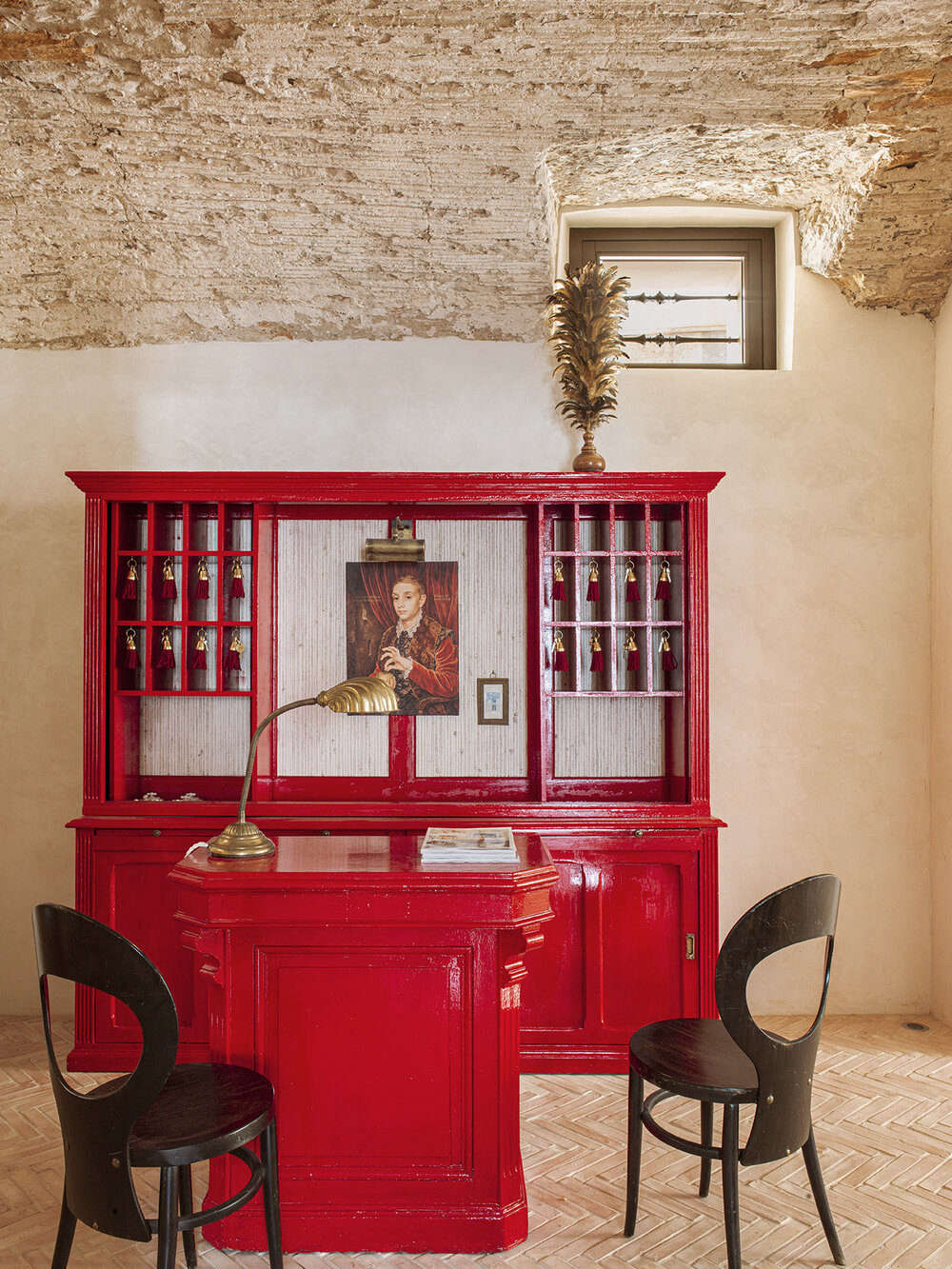 Just add red lacquer: the front desk was created from two flea market pieces renewed with glossy paint and key slots added by a local carpenter. The surfaces here range from newly laid herringbone brick (handmade in Spain) to freshly plastered walls and a ceiling preserved in its excavated state. The chairs are 60s French: the Mouette design from Baumann.