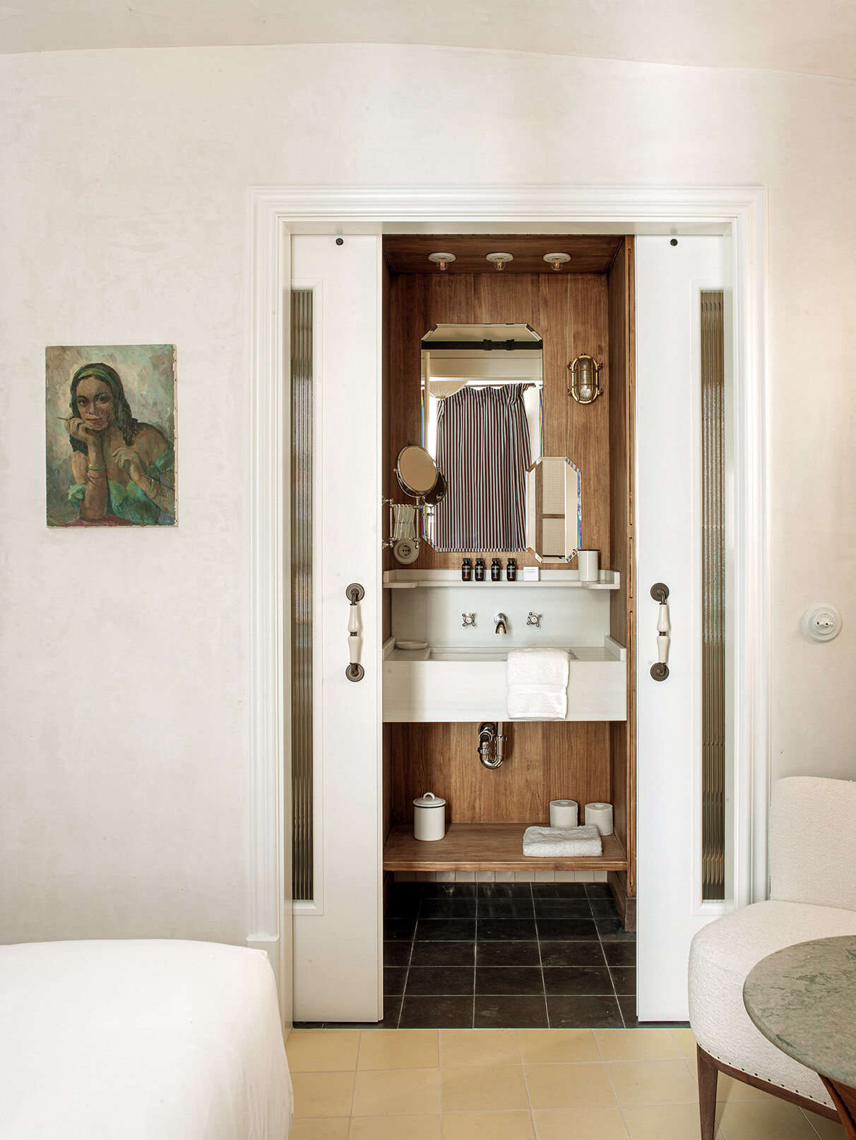 A wood-paneled bathroom with sliding glass doors and a nautical bulkhead light. The bathroom toiletries (from Grown Alchemist)—and also the cleaning products used throughout—are organic and biodegradable.