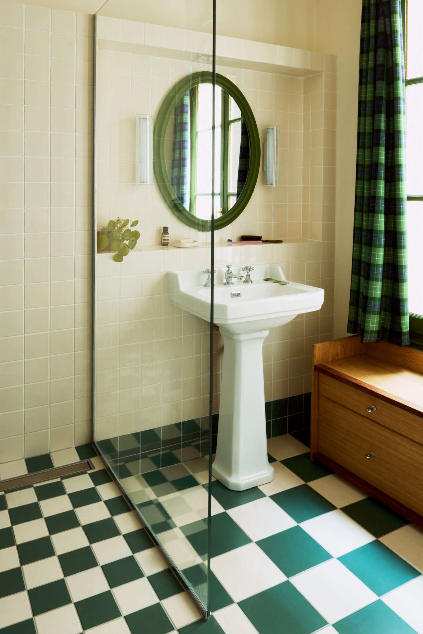 The green theme continues in the bathroom, where the bespoke drawers serve as both storage and a bench.