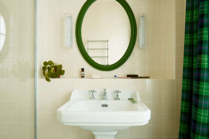 The pedestal sink stands out against ivory tiles from French company Surface. The tartan here is known as Hibernian Football Club