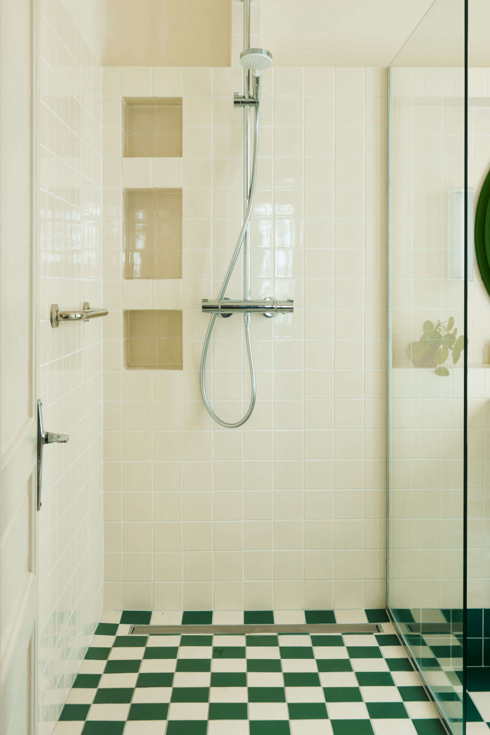 The glass shower is thoughtfully detailed with tiled niches.
