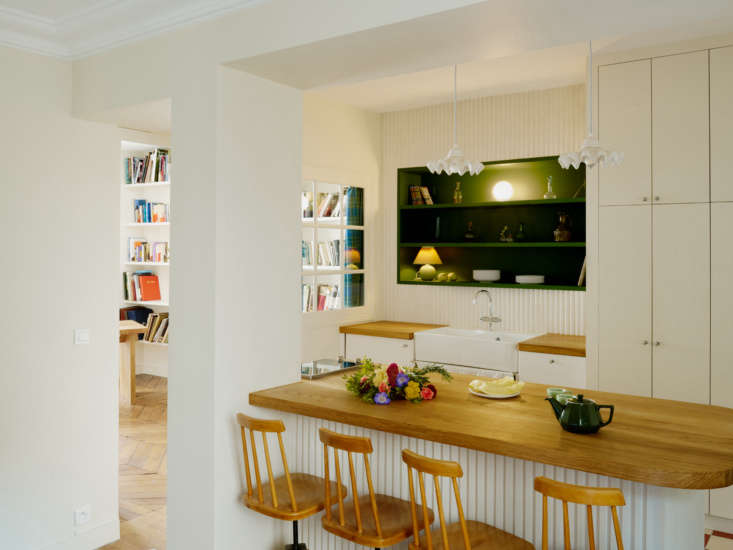 The new kitchen is now the center of the apartment, divided from the living room by a peninsula, so Stephen can cook while chatting with guests. The sink cabinets are from Ikea with custom solid oak counters and 60s Czech wooden stools.