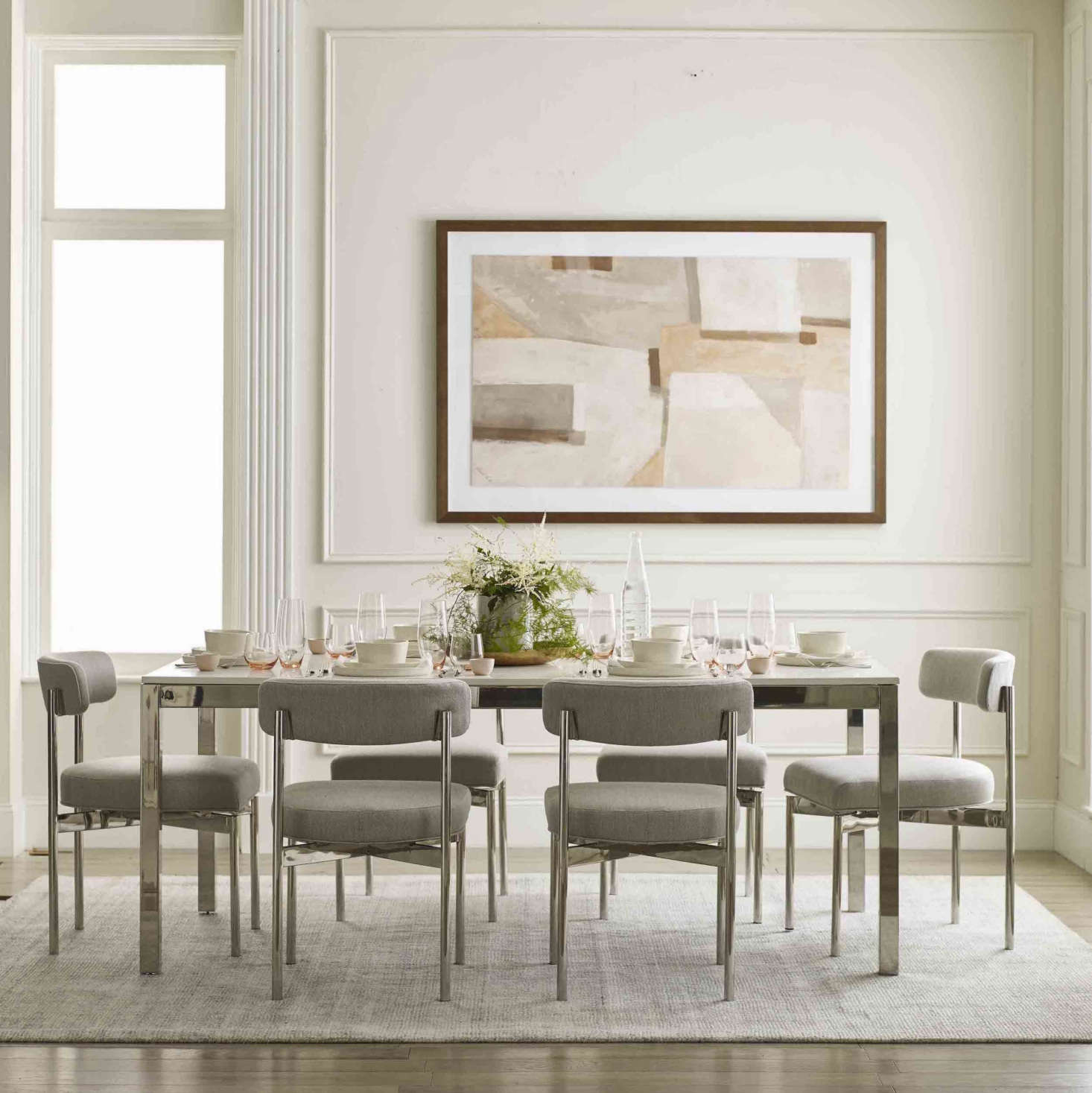 An example of the collection's multifunctional, completely customizable offerings: The Essential Parsons Dining Table is available in three sizes (60-inch, 76-inch, or 96-inch rectangle), four metal finishes (brushed brass, brushed stainless, pewter, and polished stainless, shown), and three tops (white quartz with or without veining and gray quartz) to suit any style and need. Choose the small version for a dining table that's also easily used as a desk or a larger design for at-home family dinners. It's shown with the Remy Dining Chair, available in matching finishes.