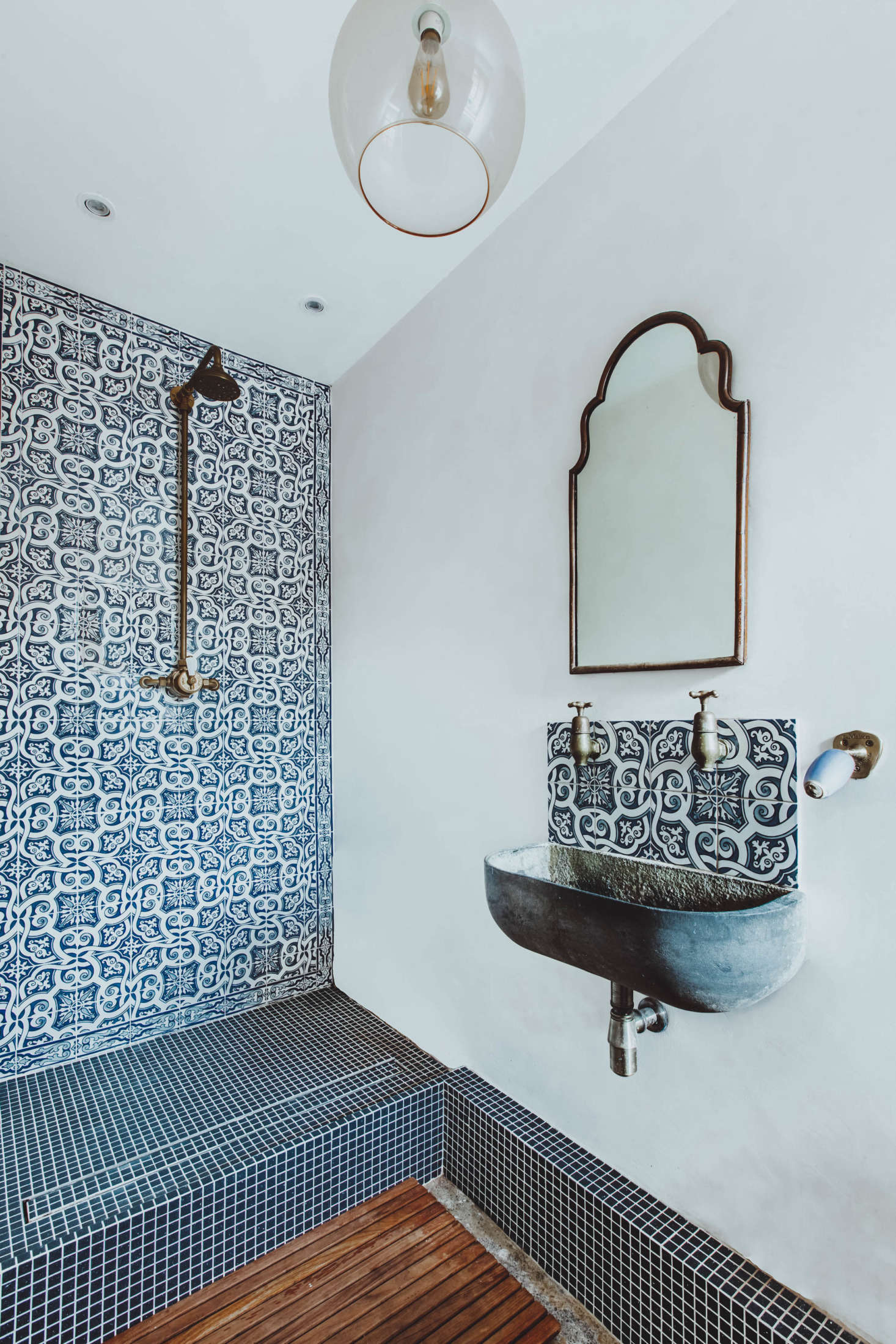 In one bath, the shower is tiled with Portuguese azulejo tiles. &#8