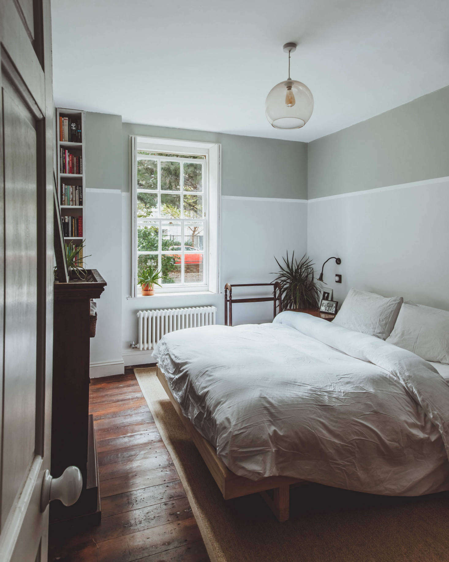 In the bedroom, dark-stained floors and a simply made bed.