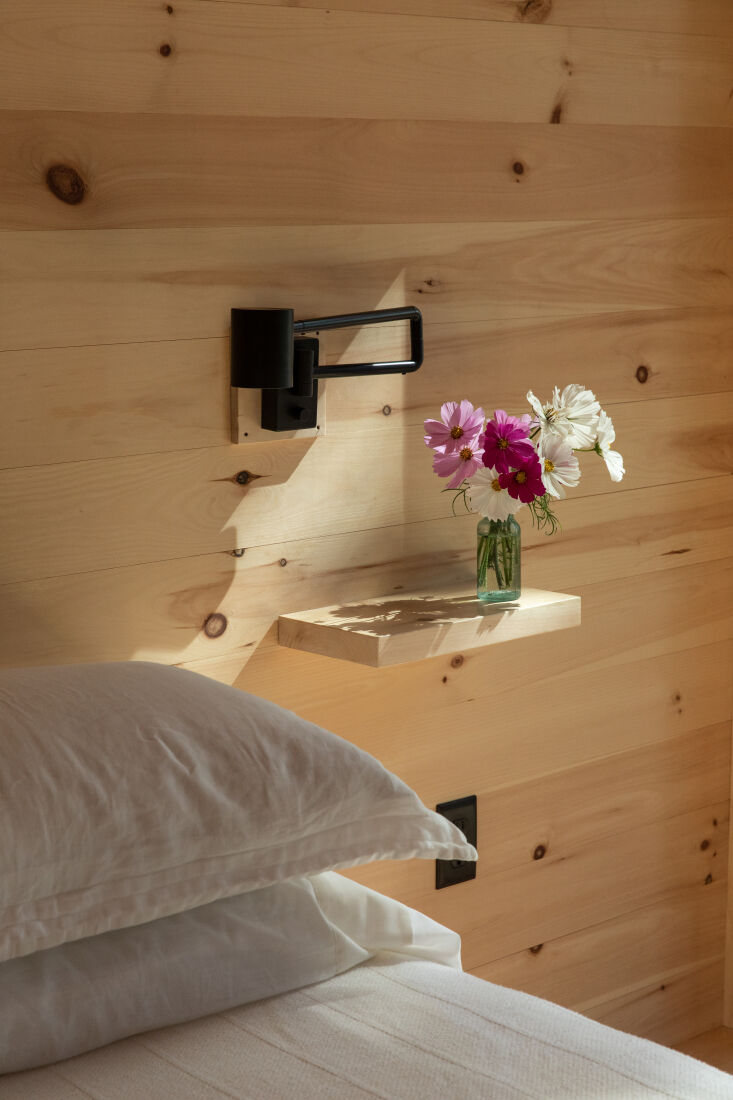 a built in pine shelf serves as a bedside table. 13