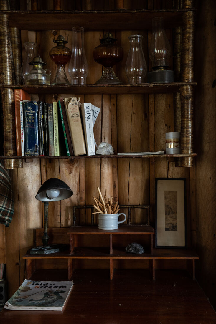 the cabin is filled with well loved reads and a collection of oil lamps. 22