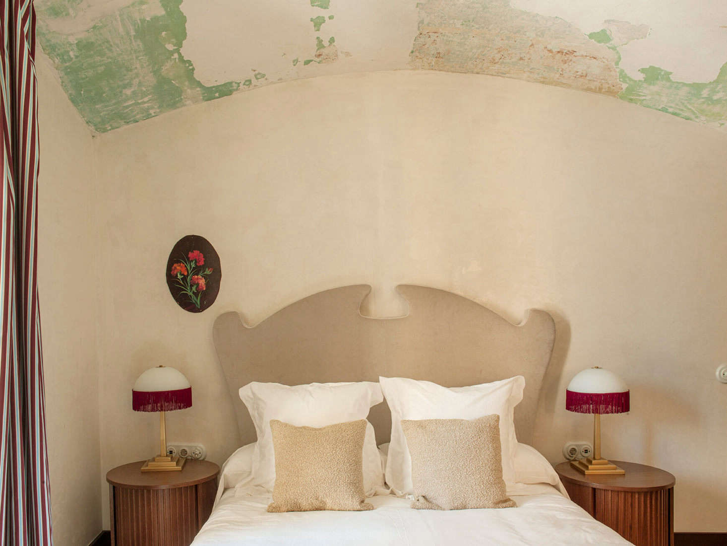 Under an atmospheric raw ceiling, a fanciful headboard flanked by fringed lamps.