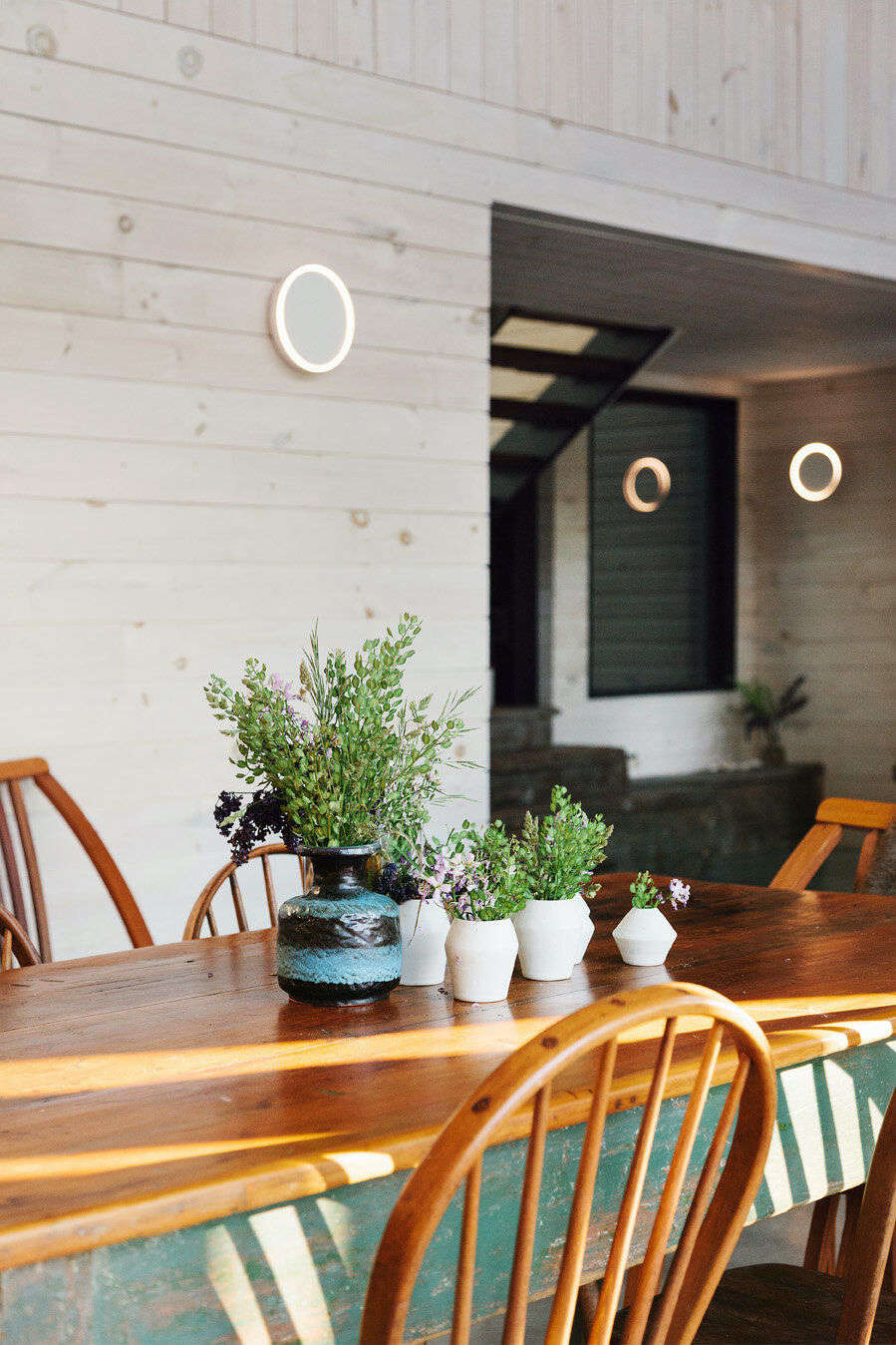 A collection of ceramic vases from Cylinder Studio on the farmhouse table. The sconces are by Anony.