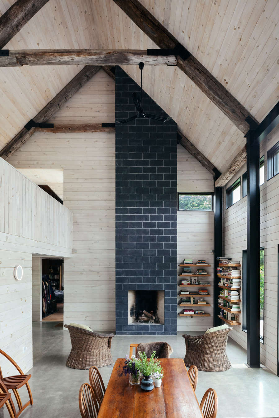 A dramatic fireplace spanning two floors sits directly across from the kitchen. The surround is made up of charcoal-colored concrete blocks.