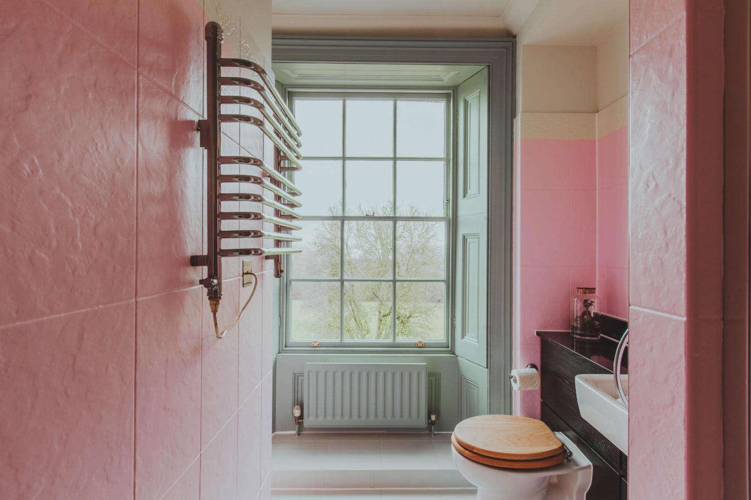 A bright pink tiled bath.