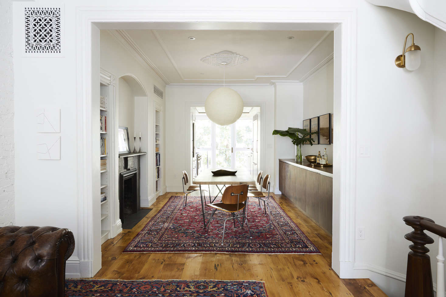 The rooms are arranged enfilade: just beyond the front door, the living area opens to the dining room and a view of the new window wall in the kitchen addition. Openings between rooms were enlarged—carefully: &#8