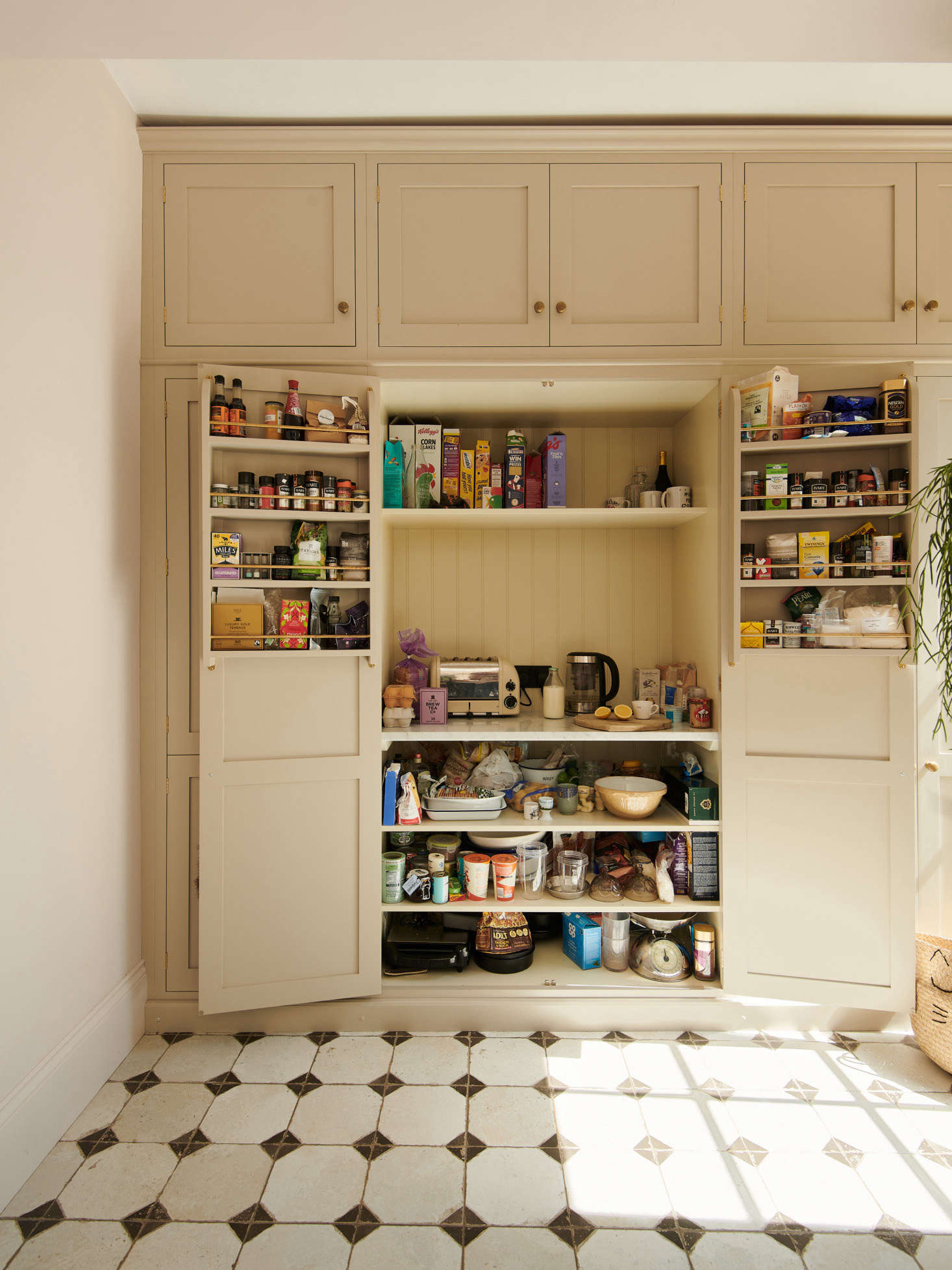 Adjacent to the refrigerator is the pantry. An electrical outlet inside means Chris can store the toaster and tea kettle on the middle shelf.