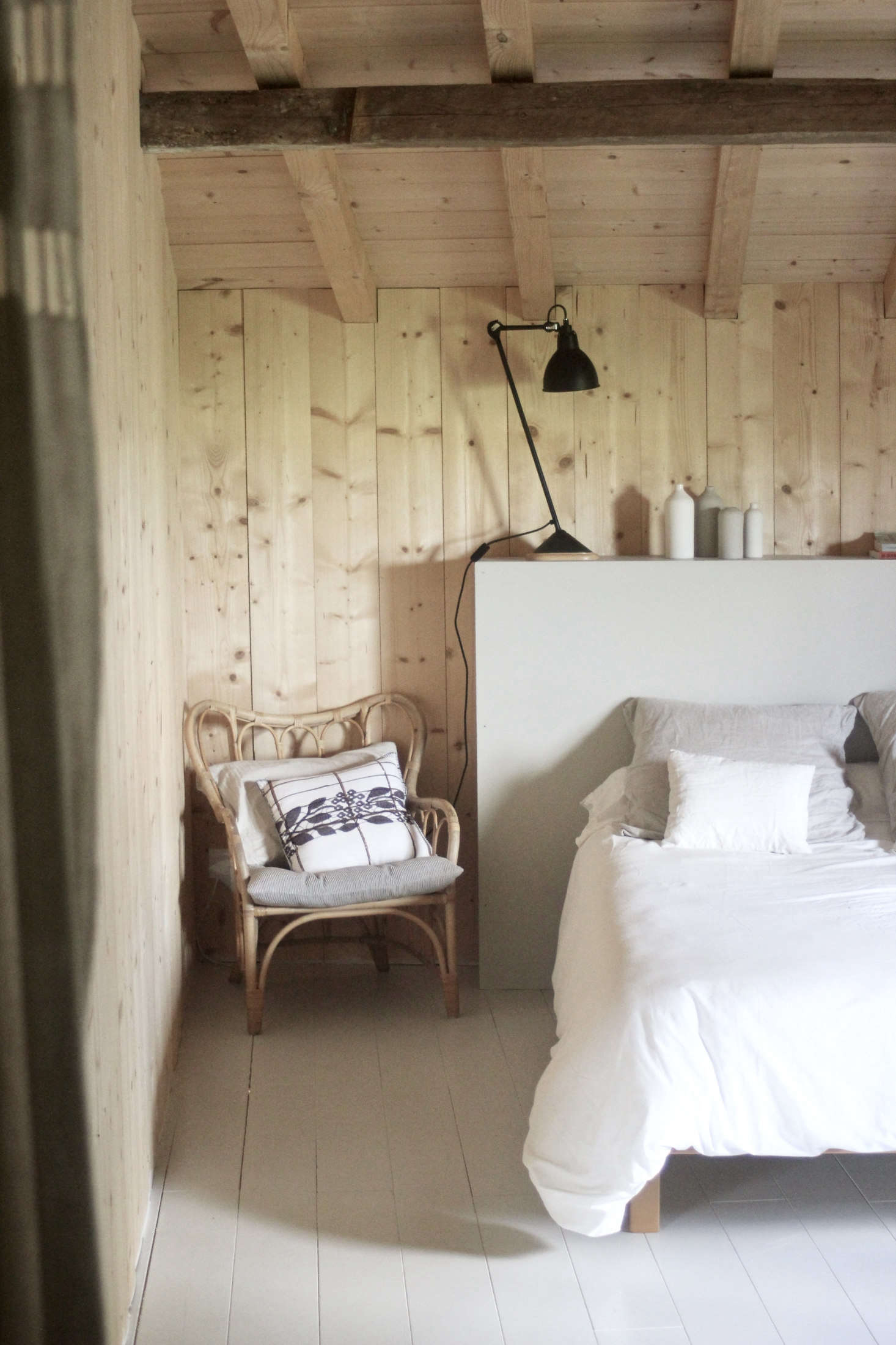 The bedrooms are paneled in pine boards salvaged from the roof and have wooded floors painted, like the homemade headboard, are in Farrow & Ball&#8