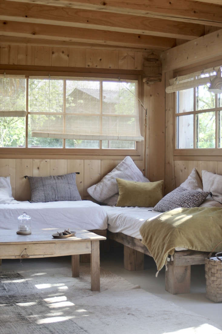 Jean built the living room daybeds out of wood from the old roof, and the couple installed the horizontally-oriented windows themselves. &#8