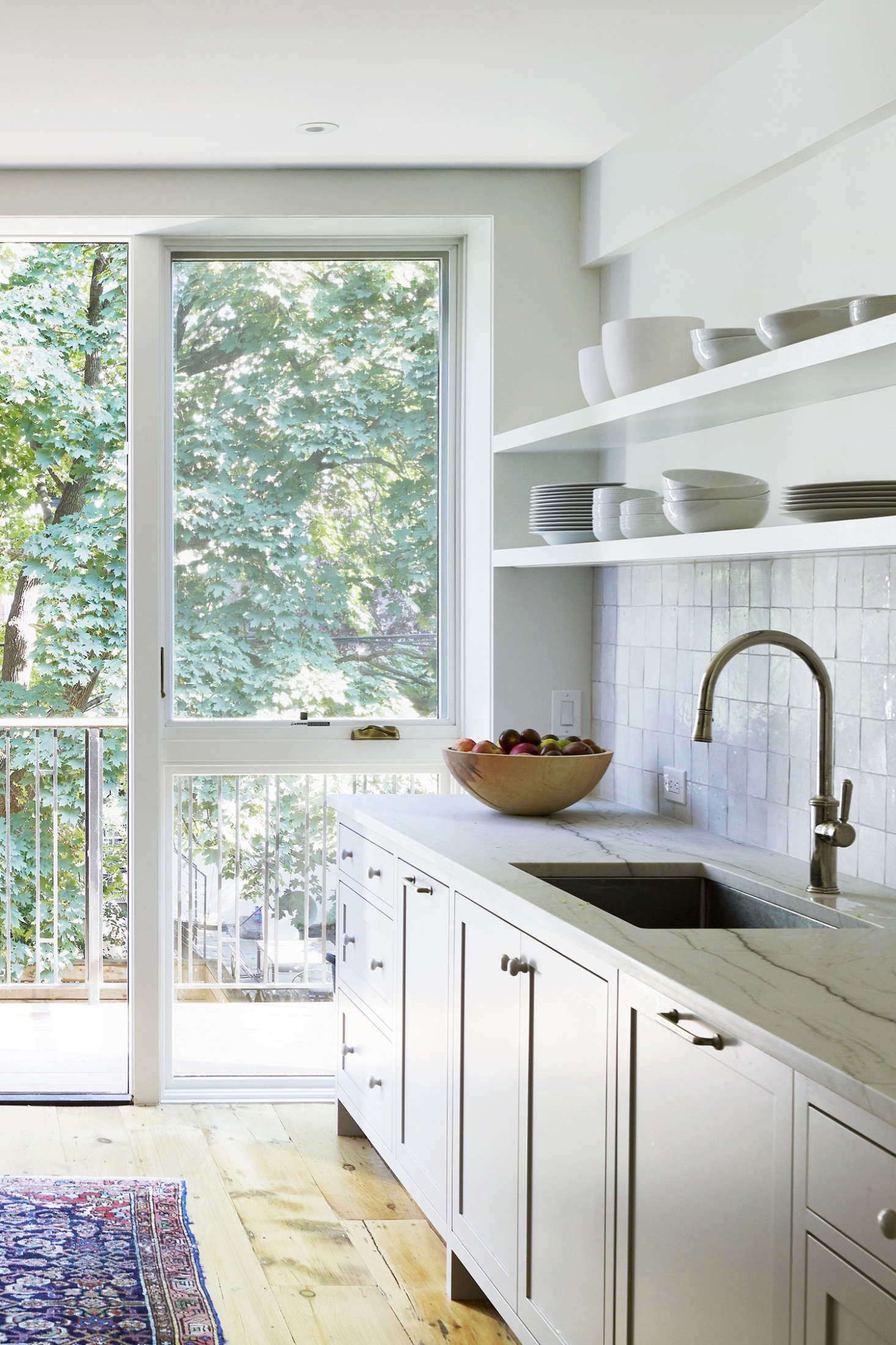 The owners are avid cooks and bakers; in lieu of a work island, they asked that the counters be extra deep. The cabinets are a custom design with Aria Quartzite counters from SMC Stone. The kitchen woodwork was shop spray-painted in Farrow & Ball&#8