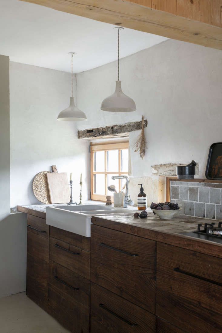 The kitchen cabinets are redwood stained brown and detailed with tiles of white-glazed black clay that the couple made themselves. The Limoge porcelain Point Suspension Lights are a longstanding Epure design.