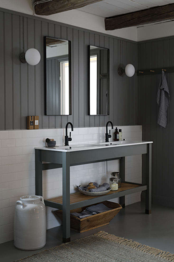 Italian sinks with Dornbracht Tara faucets are set in a Kvänum vanity with slatted storage. The subway-tiled backsplash meets beadboard paneling in a warm gray from Norwegian paint company Jotun (NCS code 650