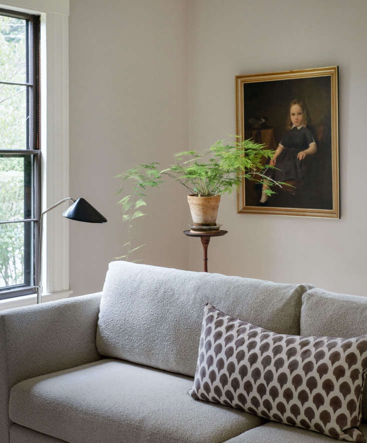 """A detail of the sofa in soft boucle fabric, paired with a painting passed down in Justine's family and a spindly fern. """"Sitting comfortably has so much to do with what's inside our sofas,"""" notes Allison, """"from the sustainably sourced solid-wood frames to our exclusive Signature cushions, designed to bounce back when you stand up."""""""